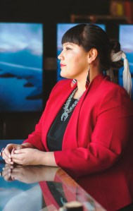 a woman in profile with dark hair, red jacket and turqoise necklace