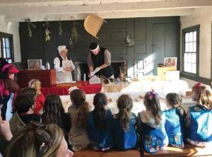 A group of school children sit in front of a demonstration of historic cooking methods.