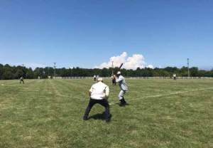 Two men stand on a baseball field one pitching and one catching.