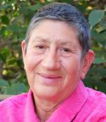 Headshot of Elaine Heuman Gurian with short dark and silver hair wearing a pink shirt.
