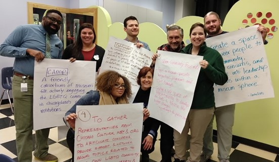 A group of eight individuals participating in CAMP hold up signs with sentences written on them proposed to be included in the group's mission statement, designed to make museums more friendly and inclusive to LGBTQ people.