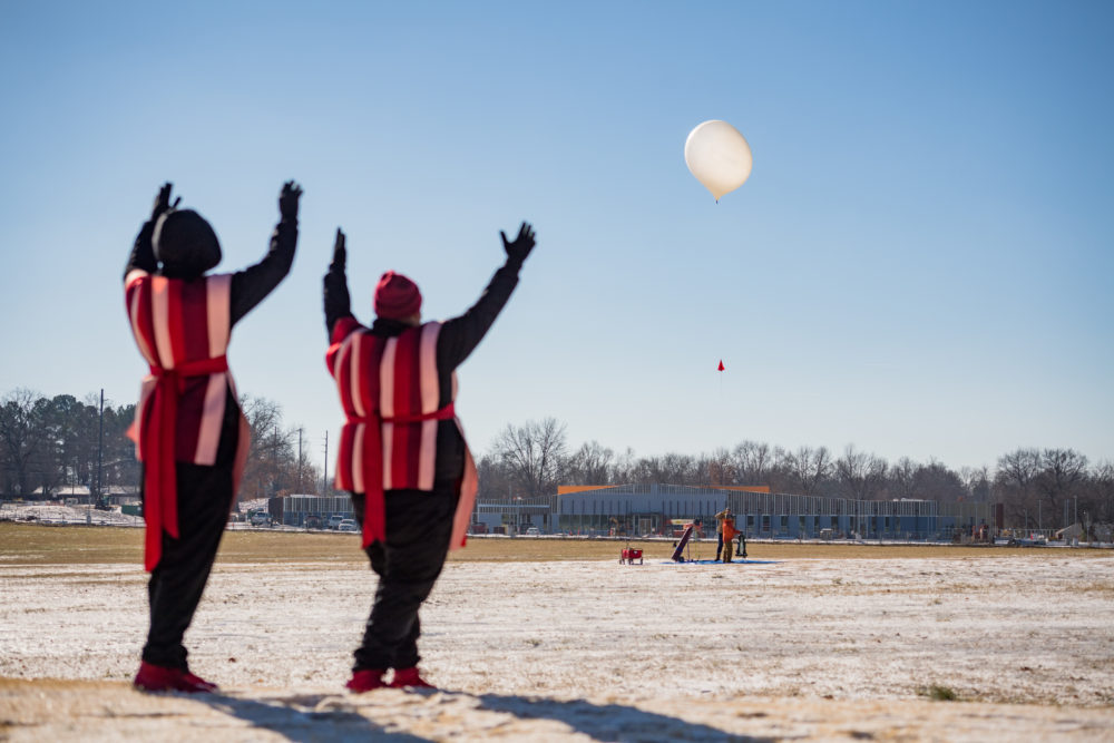 Two people wearing matching outfits face away from the camera and toward the weather balloon in the distance, which is beginning its ascent to space.