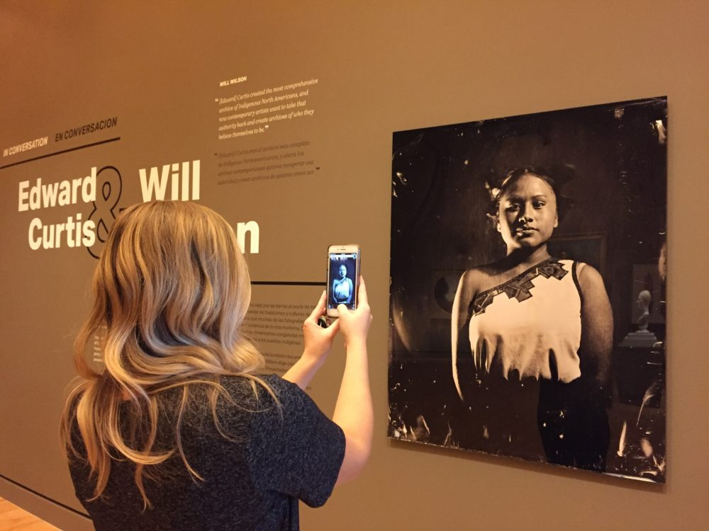 In an exhibition gallery a visitor stands in front of a photograph of a Native American woman. The photograph is rendered on the visitor's phone screen.