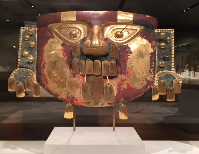 A gold Peruvian mask of a stylized face