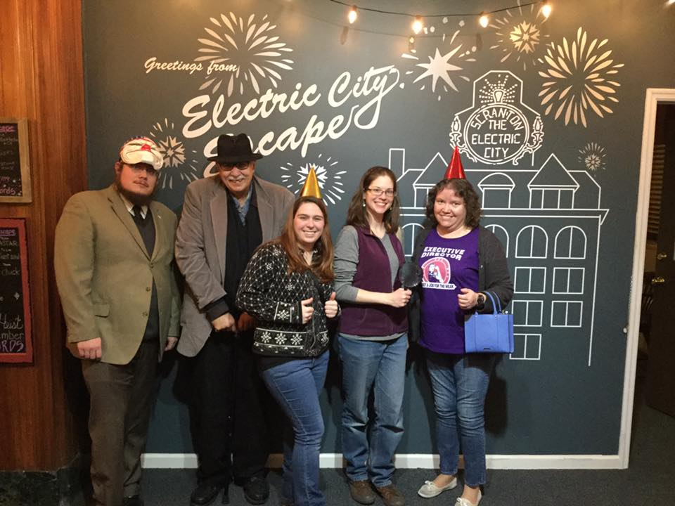 "The staff of Luzerne County Historical Society pose for a group portrait in front of a wall mural that says ""Greetings from Electric City Escape; Scranton, the Electric City."""