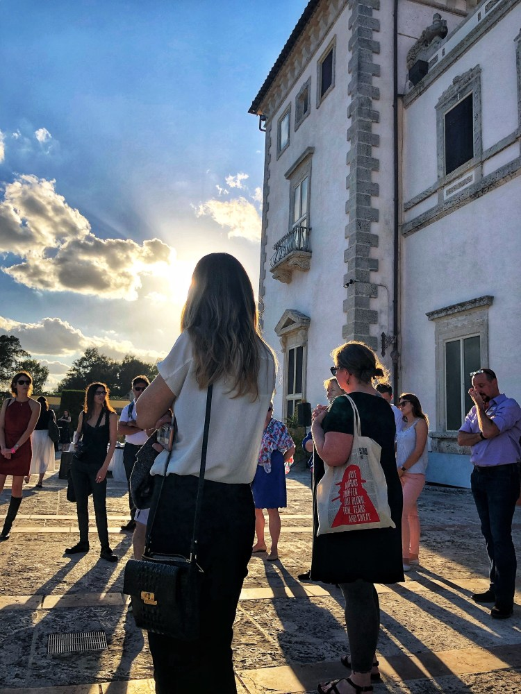 A group of people stand in a circle talking in front of Vizcaya Museum and Gardens.