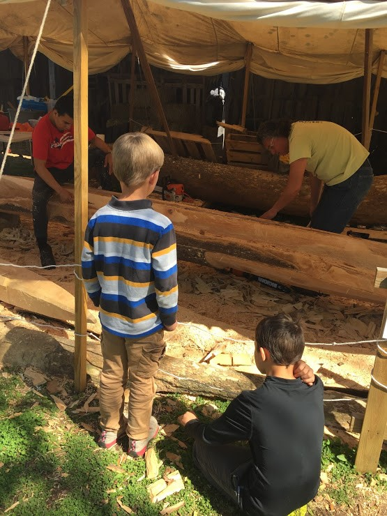 Young visitors watch two workers work to carve a large tree under a canopy tent outside.