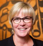 Woman with short blonde hair and dark glasses smiling