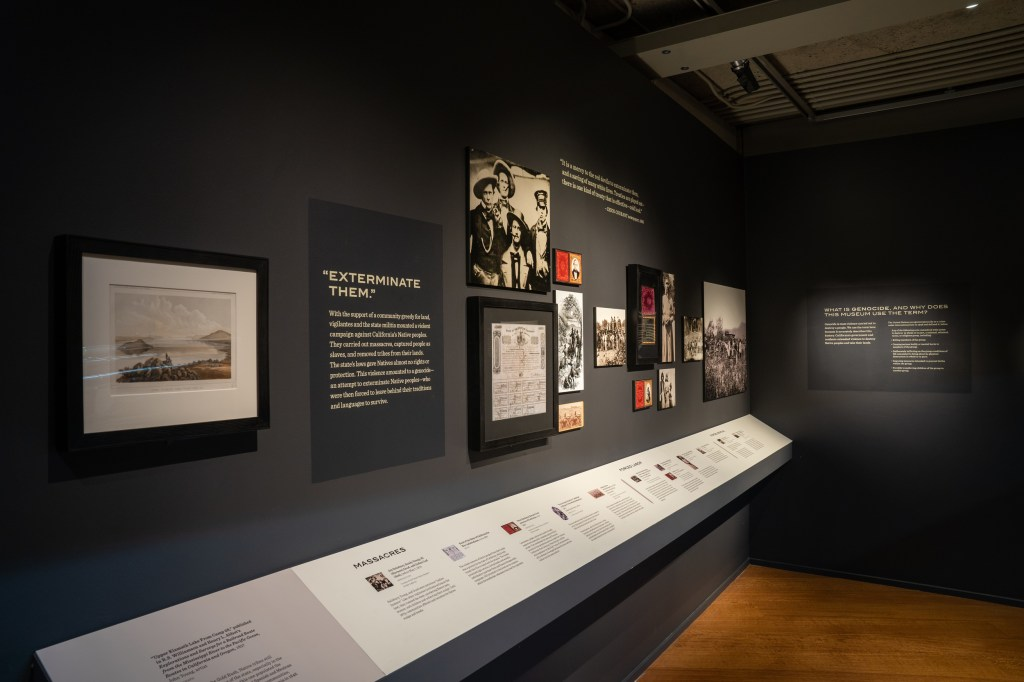 "A historical timeline is seen, with framed photos and documents illustrating the history described. The title ""Exterminate Them"" is visible."