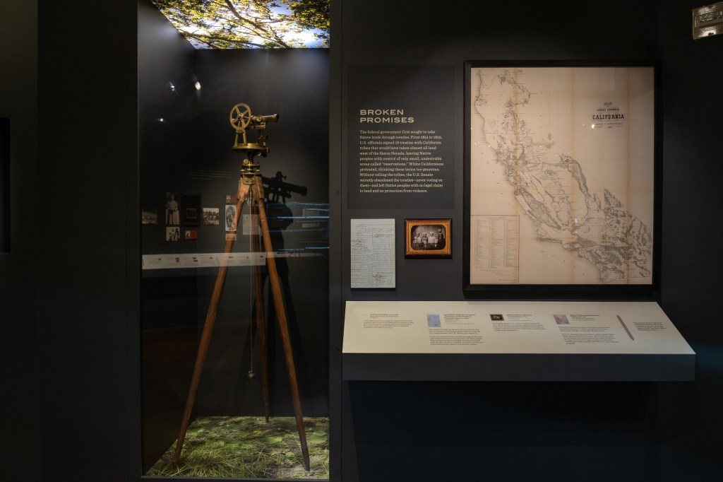 "A view of the ""Broken Promises"" section, with a land-surveying tool, a map of the state of California, and several framed documents visible."