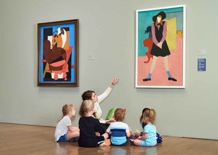 A group of children is seen in front of the painting the label describes with an adult guide. The painting is of a young woman, rendered in flat blocks of color and stylized forms.
