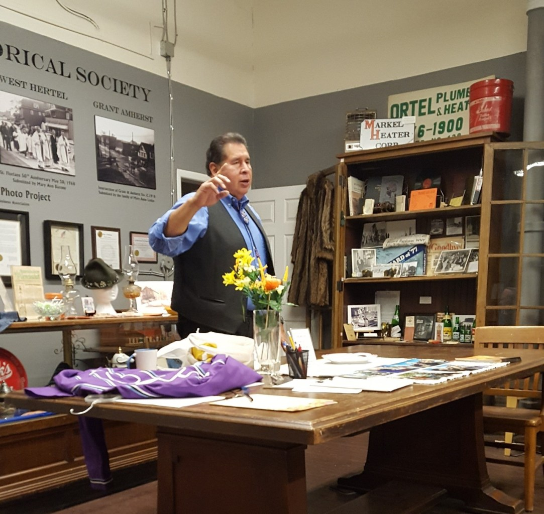 Jemison is seen in front of a table displaying artifacts as he speaks to the group.