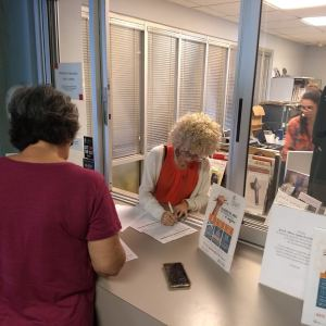 A visitor comes to a front desk to enroll in the program.