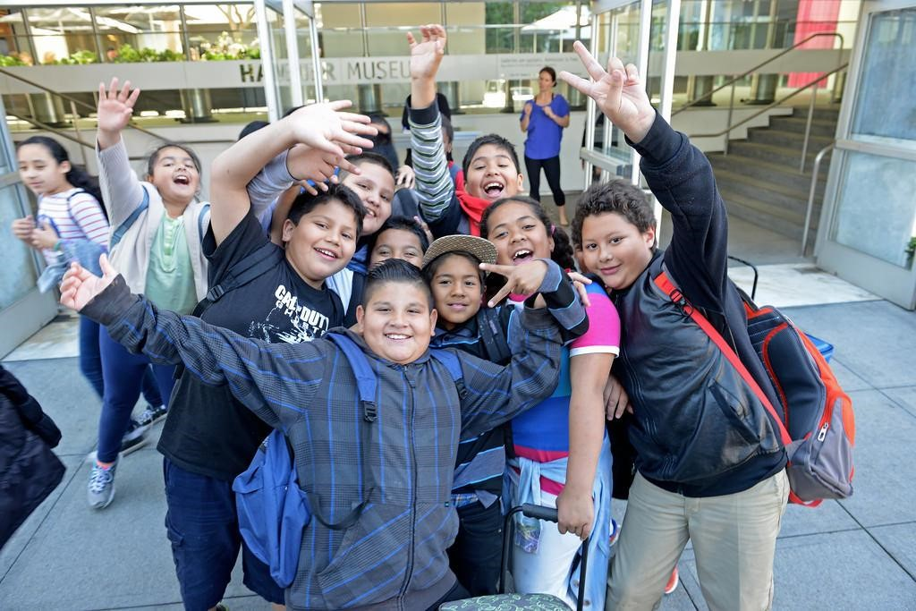 A group of exuberant students poses outside the front door of the museum, where they appear to be leaving.