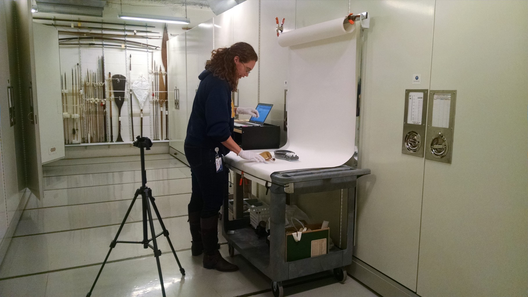 A museum employee stands at an imaging station with an object laid out on a white sheet of paper, and a camera pointed at it.