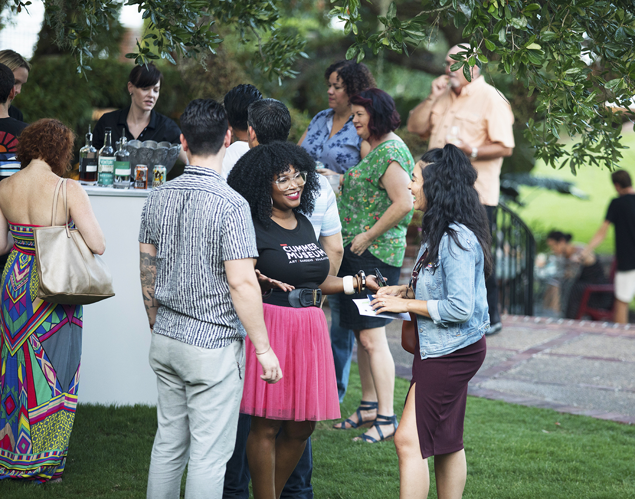 Attendees congregate outside near a bar and engage in conservation.