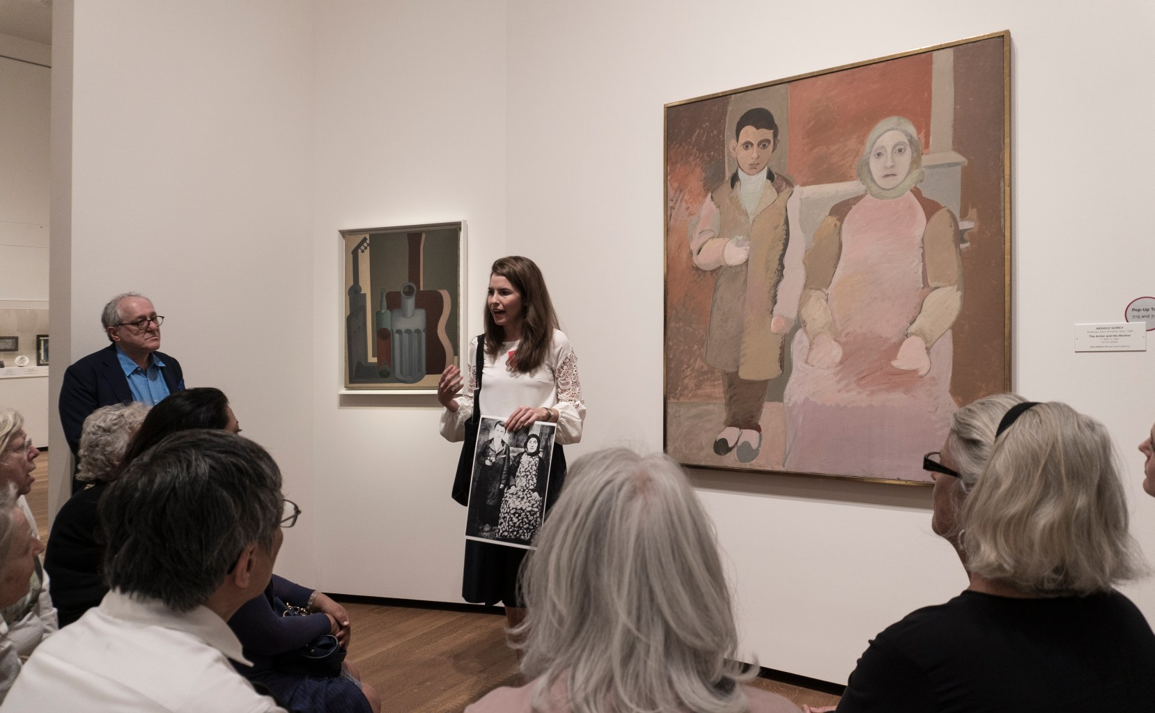 An educator stands in front of a painting addressing a seated group of participants. The painting behind her shows a standing child and a seated adult, and is rendered in flat blocks of earth-toned color. The educator holds up a print-out of a photograph of the subjects in real life.