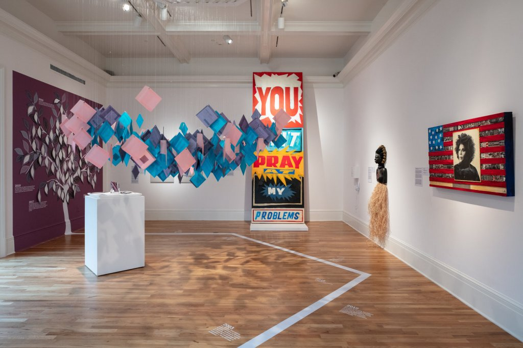 """A variety of artworks in a museum gallery: pieces of paper suspended from the ceiling, a large drawing of a tree, and a piece that says """"You can't pray at my problems"""" in bold lettering. A timeline in white font is visible on the wood floor."""