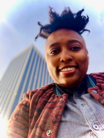 Lanae posing for a selfie with the camera below her and looking up at a tall building and the sky in the background.