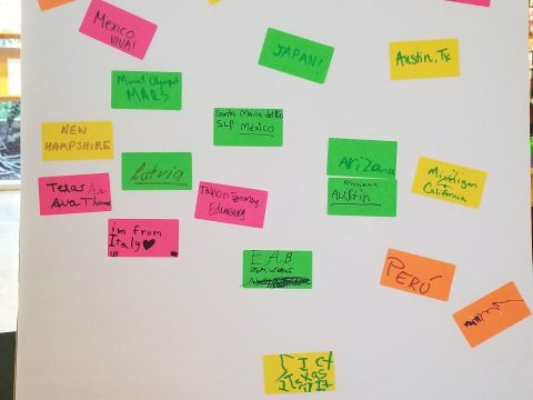 """A large sheet of paper with """"Where are you from?"""" written at the top, with colorful sticky notes below that say answers like """"Portugal,"""" 'Nebraska,"""" """"Ohio,"""" """"Mexico City,"""" """"Mexico / VIVA!,"""" """"JAPAN!,"""" and """"Austin, Tx."""""""