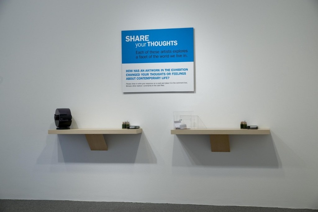 """Two floating shelves with note cards, pencils, and a rolodex on them, beneath as sign that says """"Share your thoughts: Each of these artists explores a facet of the world we live in. How has an artwork in the exhibition changed your thoughts or feelings about contemporary life?"""""""