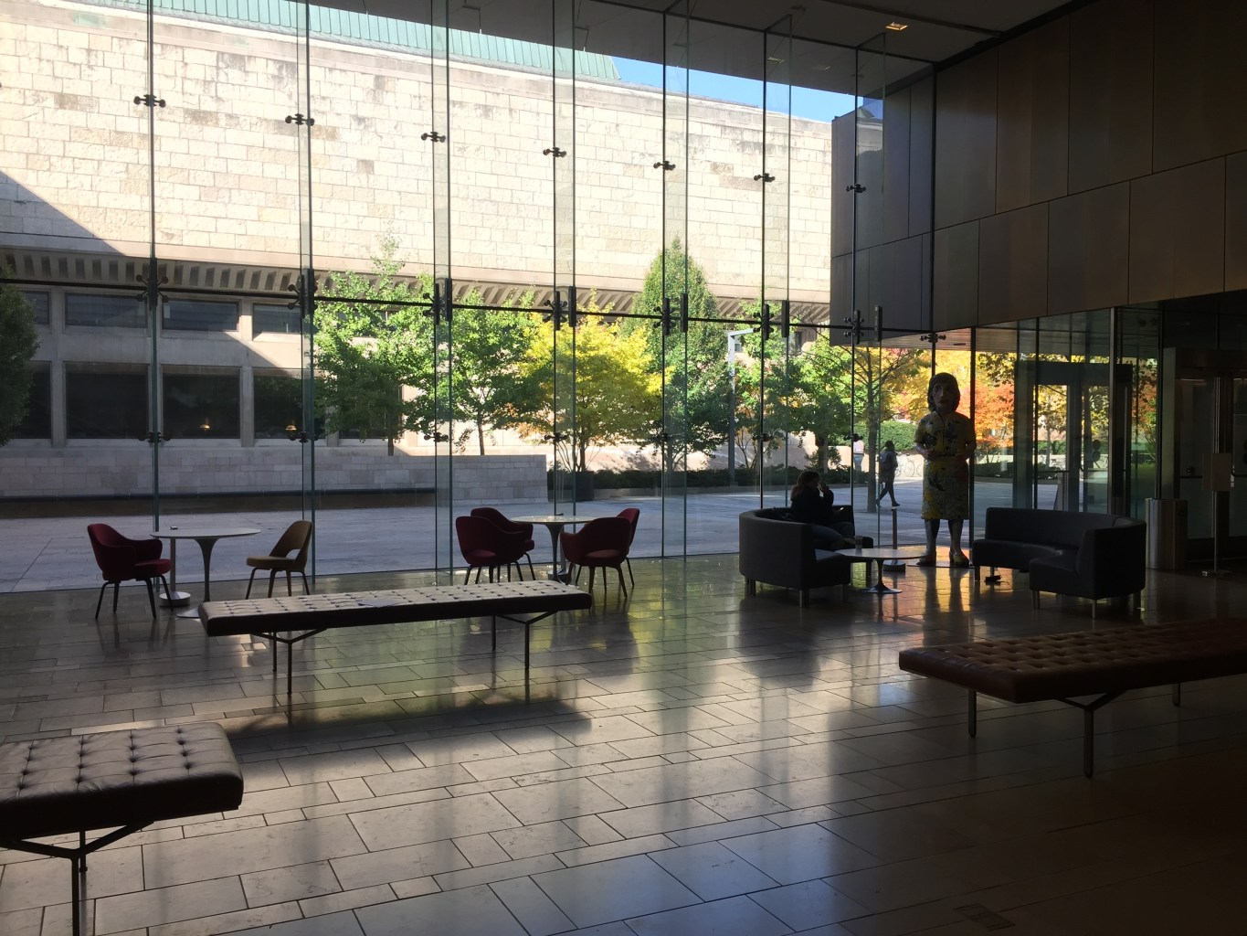 A lobby space with floor-to-ceiling glass walls and cafe-style tables and benches.