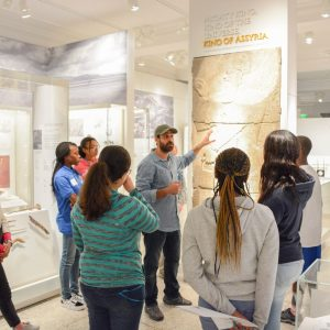 A gallery tour with a Global Guide speaking and gesticulating toward a graphic on display.