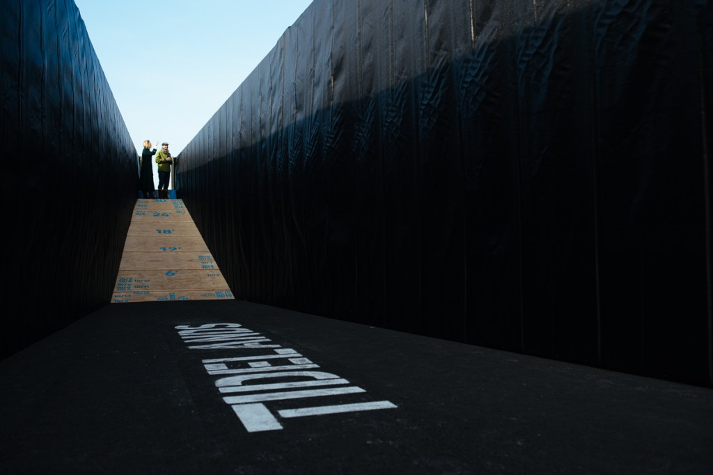 """A ramp leads to an underground cavity where the word """"Tidelands"""" is painted on the ground."""