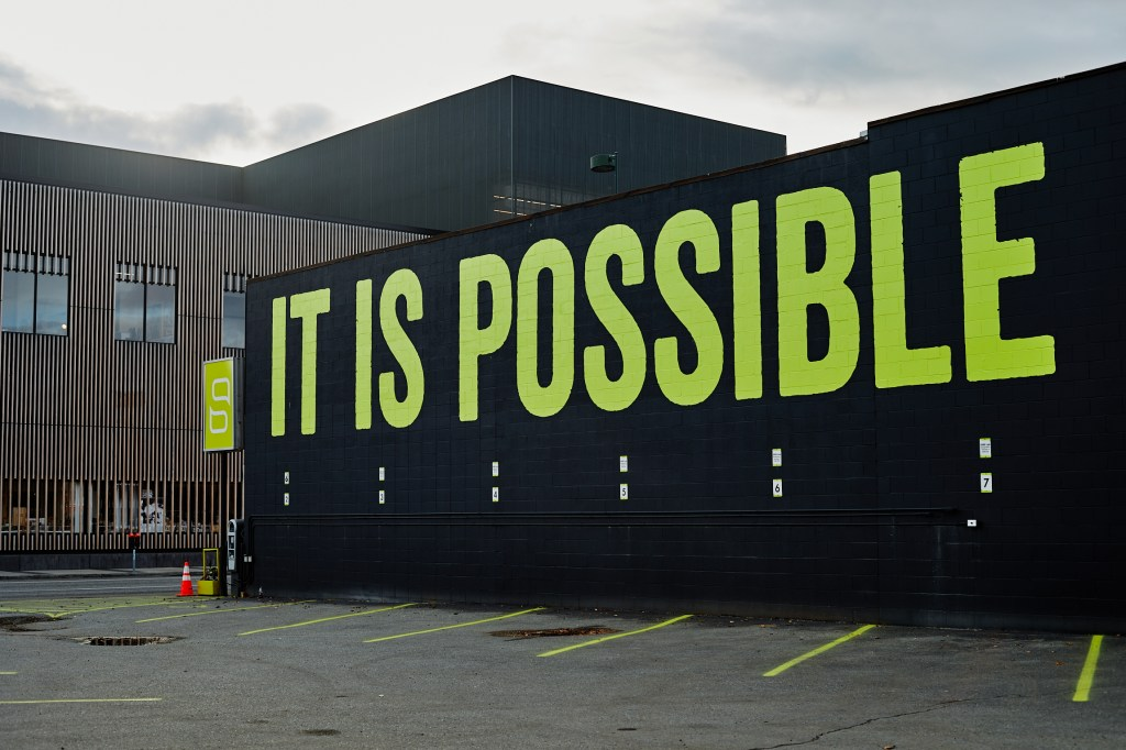 "A black-painted building with bright green lettering reading ""It is Possible"""