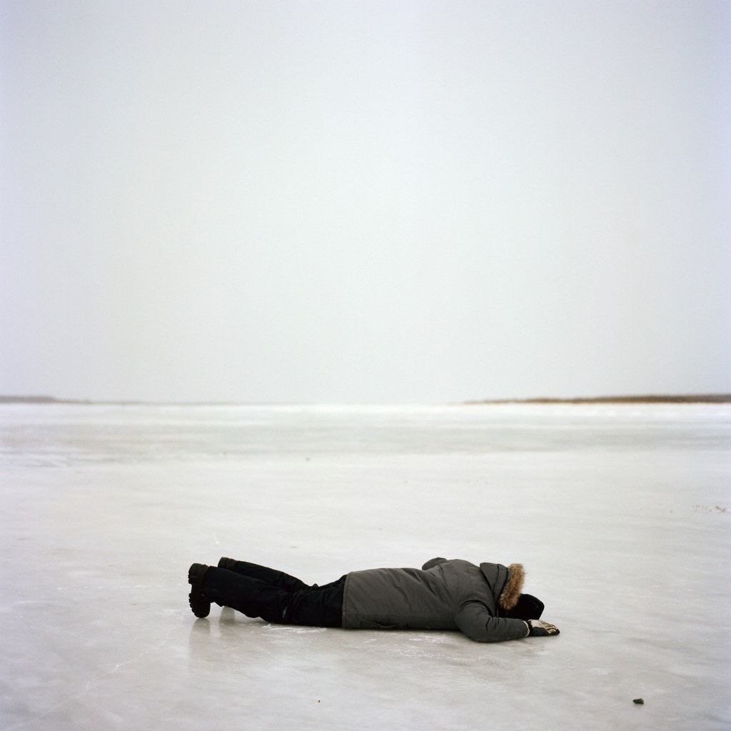 A person lying flat on a frozen river