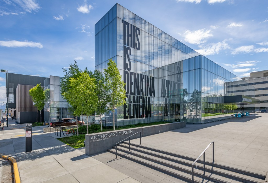 """A glass building facade with large letters reading """"This is Dena'ina Elnena"""""""