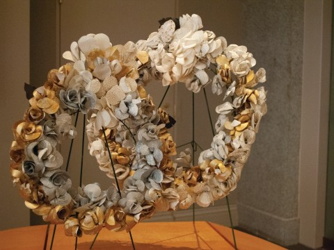 Two white, silver, and gold wreath's sit in a corner.