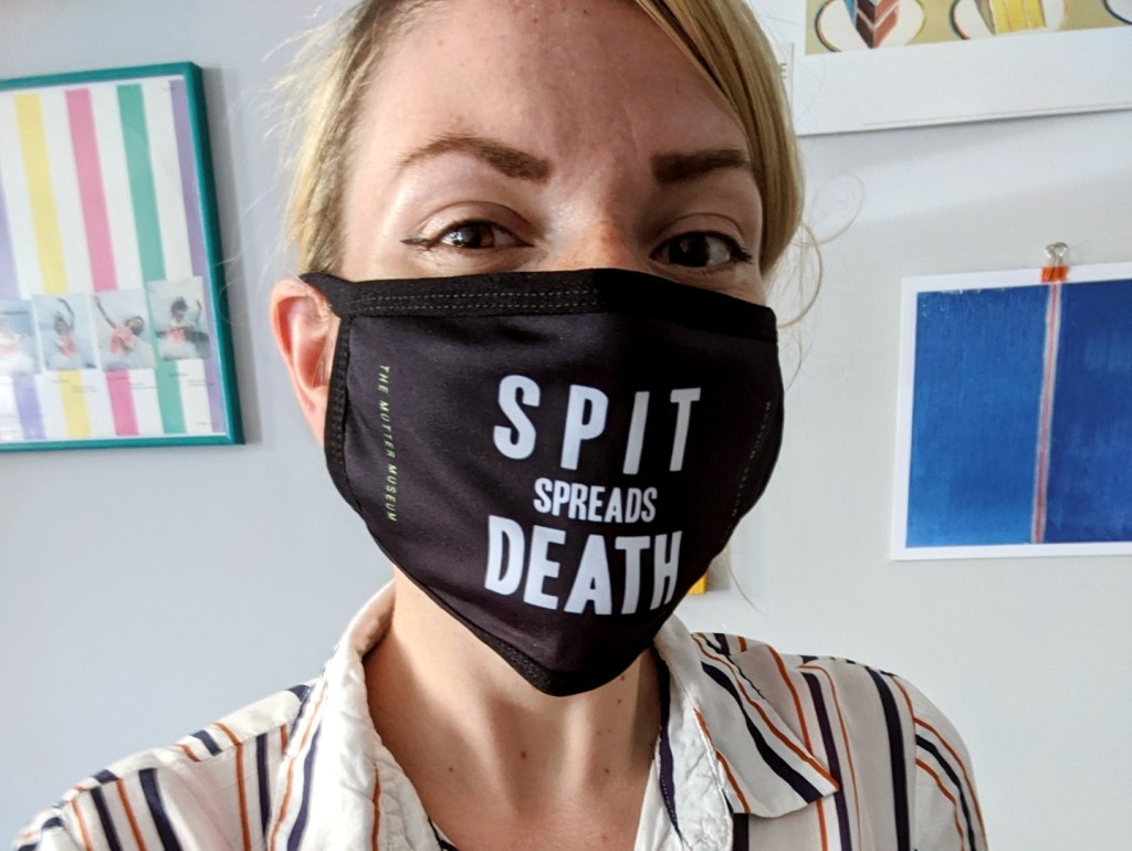 "A person posing in from of hanging prints wearing a black mask reading ""Spit Spreads Death"" in white lettering, with the name of the museum printed on the side."