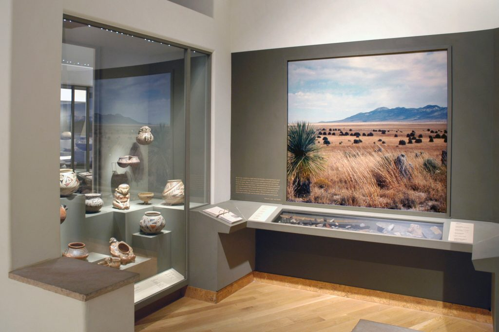 An exhibition gallery of pottery and a photograph of a desert landscape
