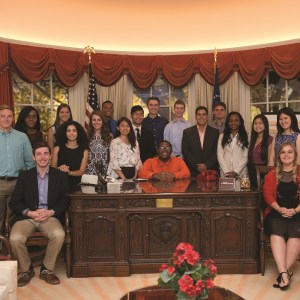 A school group posing behind a desk in the replica of the oval office.