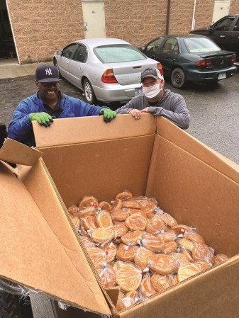 Two men, one wearing a mask, load 250 loaves of donated fresh-baked bread onto the truck.