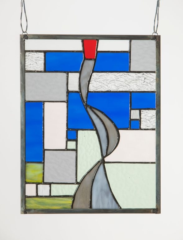 A stained glass piece with abstract grid and curved lines