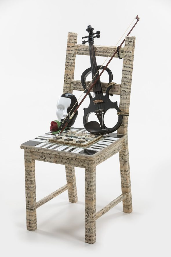 A chair wrapped in a sheet music print with a violin, opera mask, and rose on top