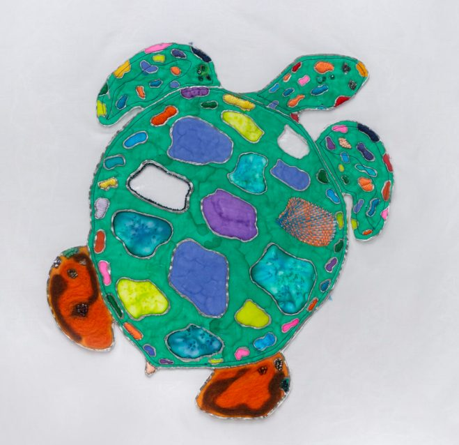 A textile rendering of a sea turtle with colorful patches