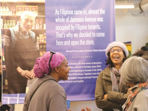 Several women stand smiling and laughing in front of an exhibition banner.