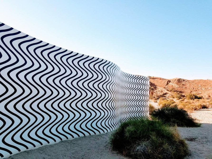 A curving wall with black squiggles against a white background in a desert setting