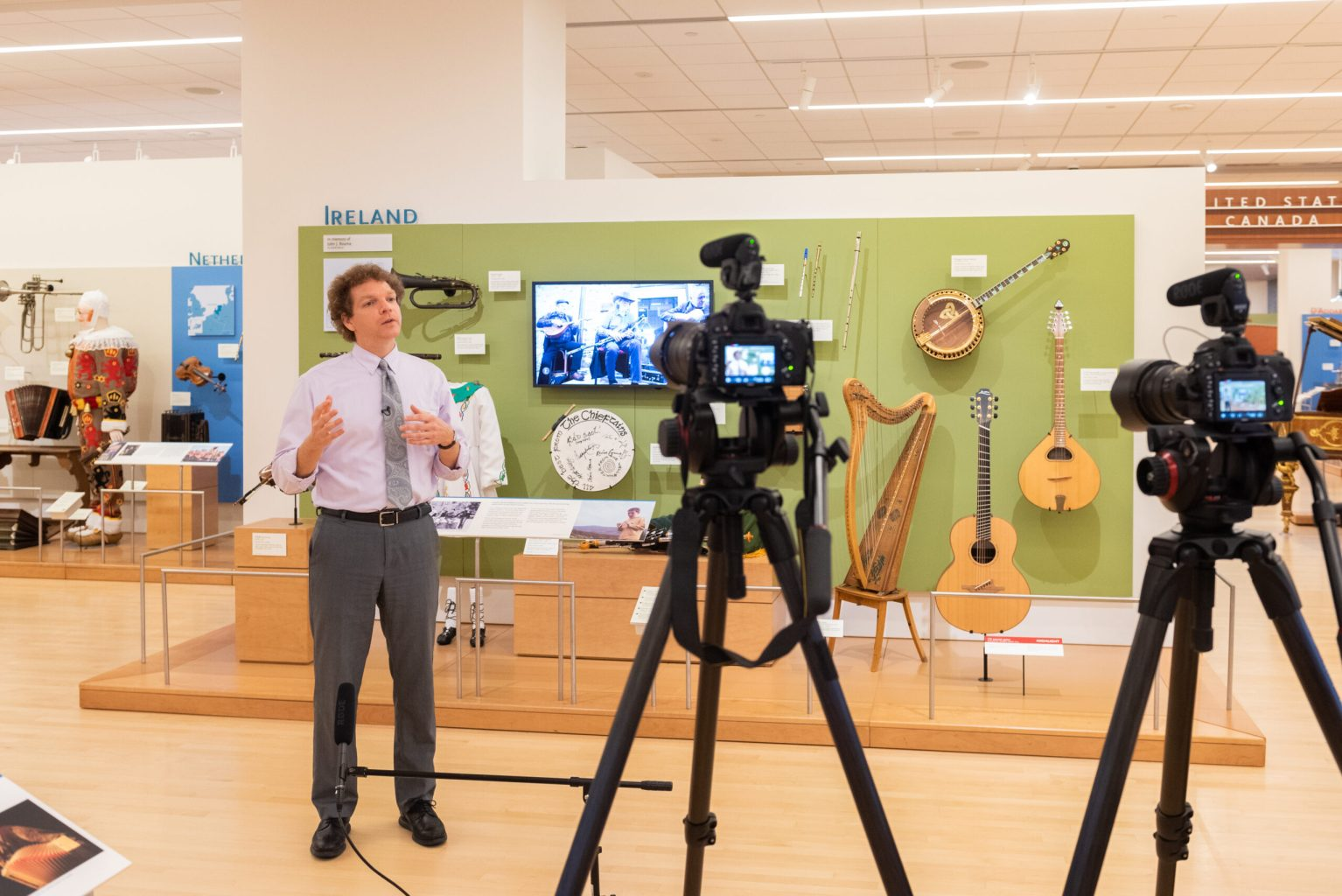 A person speaking in a museum gallery of musical instruments from Ireland in front of cameras