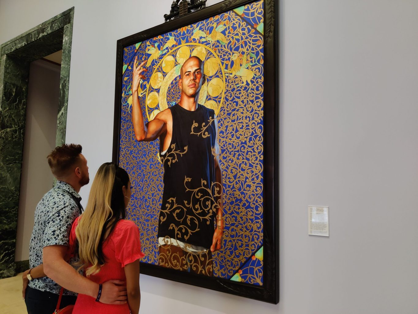 Visitors standing with their arms around each other looking at a painting of a subject surrounded by decorative spirals