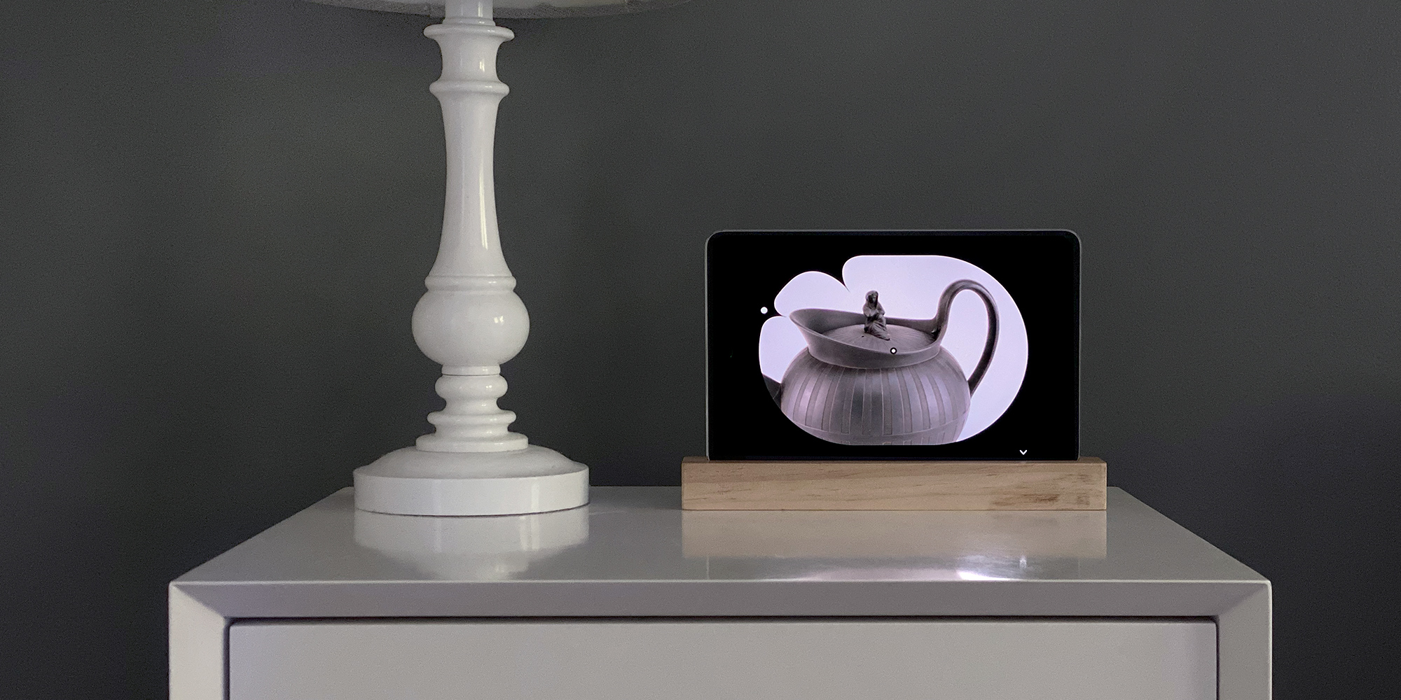 A rendering of a bedside table with a digital screen on a pedestal showing a picture of a teapot with a minimalist clock shape aligned with the teapot's spot