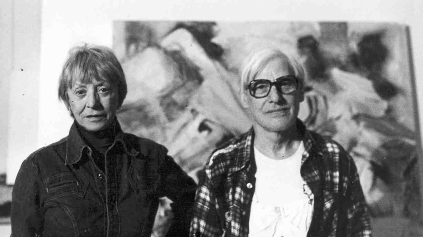 Black and white photograph of the heads and torso of Elaine and Willem de Kooning standing in front of an abstract painting