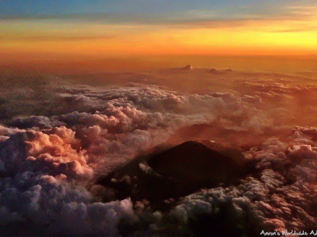 Sunset from an Indonesian aircraft as a volcano peeks through the clouds.