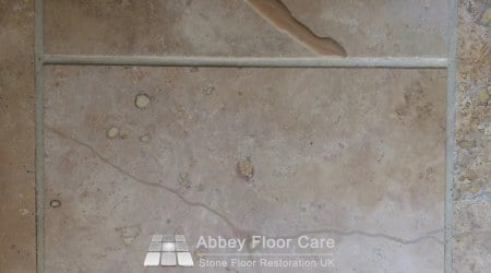 Cracks in Travertine tiles filled and then sanded smooth with the surface of the tile