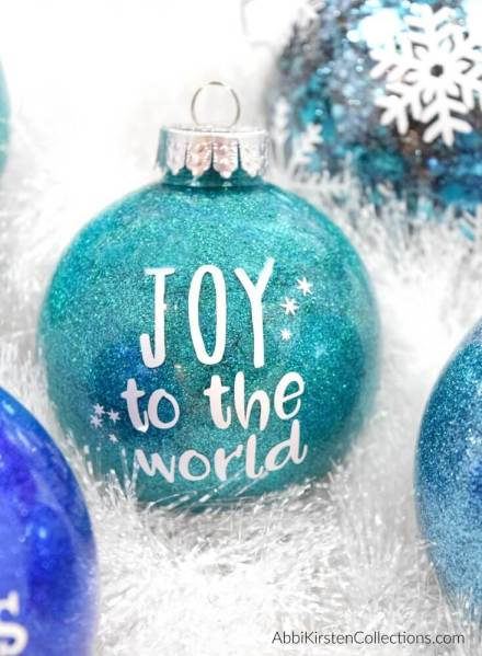 DIY Glitter Ornaments: How to make easy custom Christmas ornaments with vinyl. Free Christmas word SVG cut files and how to put vinyl on a curved surface!