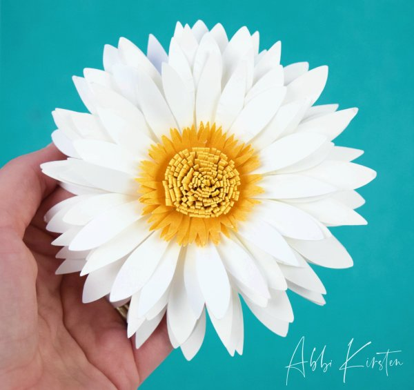 Learn how to make your own paper daisy flower blooms with this step by step tutorial. Download the templates to create your own with scissors or a cutting machine.