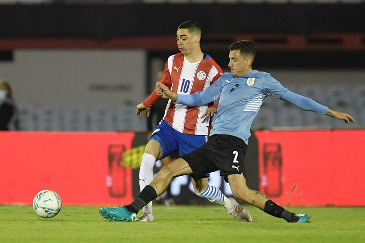 José María Giménez y Miguel Almirón luchan por la posesión del balón en el juego que terminó sin goles en Montevideo.